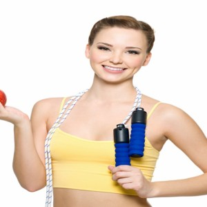 Beautiful happy fit woman with red apple and skipping rope